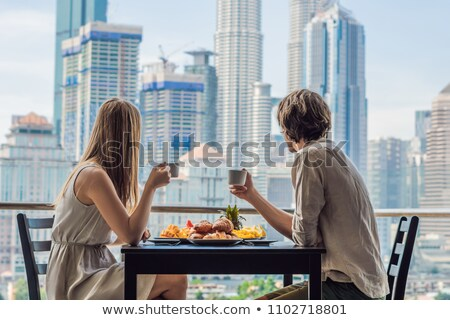 Loving couple having breakfast on the balcony. Breakfast table with coffee fruit and bread croisant  Photo stock © galitskaya