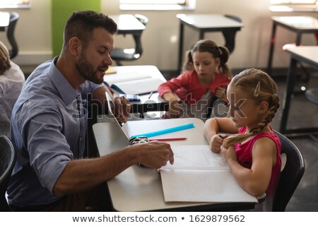 Side view of school teacher holding digital tablet and teaching in a classroom Stock photo © wavebreak_media