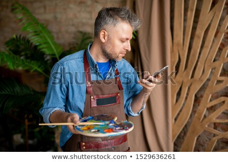contemporary creative painter with palette scrolling in smartphone stock photo © pressmaster