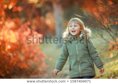 Happy girl with white hair in a warm jacket walking near the trees and breathing clean air Stock photo © ElenaBatkova