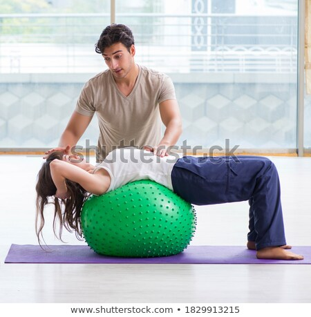 Personal coach helping woman in gym with stability ball Stock photo © Elnur