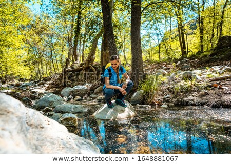 Stock photo: Hiking woman sitting on a stone in the middle of a creek passing the woods