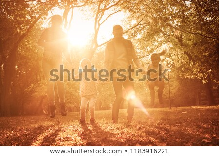 Family of four father mother and two daughters on shared walk in autumn Stock photo © ElenaBatkova