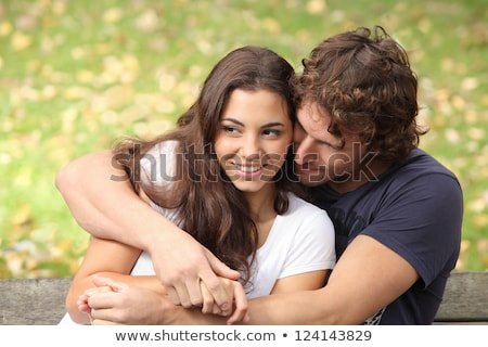 portrait of love couple embracing outdoor in park looking happy stock photo © hasloo