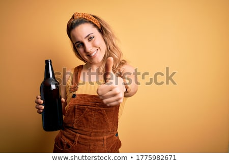 Cheerful young blonde with bottle. Isolated stock photo © acidgrey
