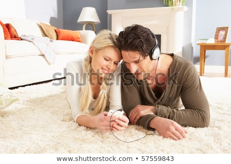 Man Listening To MP3 Player On Headphones Relaxing Laying On Rug Stock photo © monkey_business