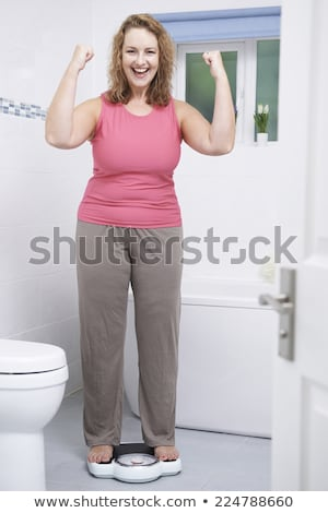 Happy Woman Weighing Herself On Scales In Bathroom Stock photo © HighwayStarz