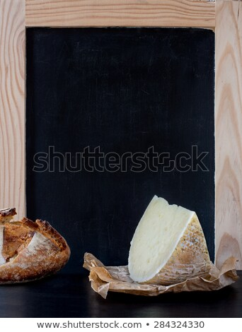 Soft cheese wedge in front of blank old blackboard carte. Stock photo © Photooiasson
