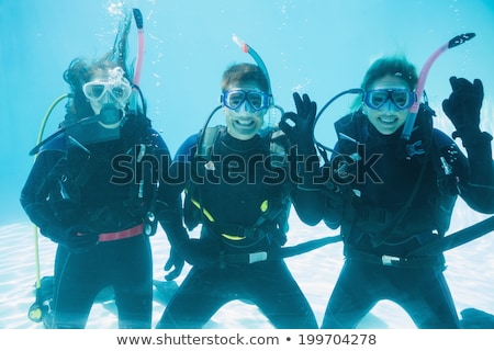 Friends on scuba training submerged in swimming pool looking to  Stock photo © wavebreak_media