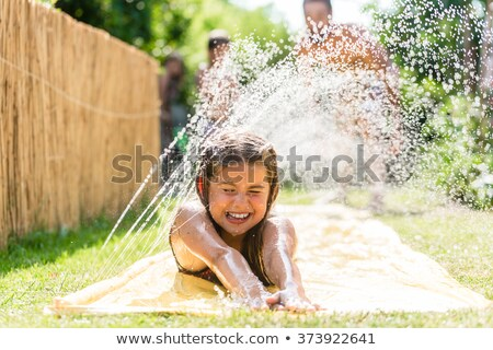 family cooling down with sprinkler in garden stock photo © kzenon