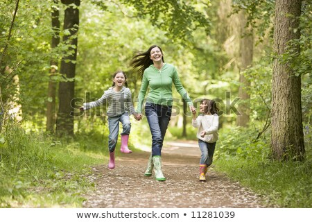 mother and children running along woodland path stock photo © monkey_business