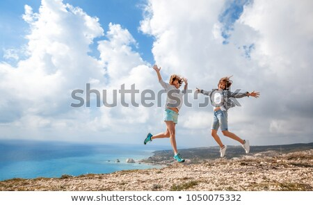 two young girls jumping on hill stock photo © is2