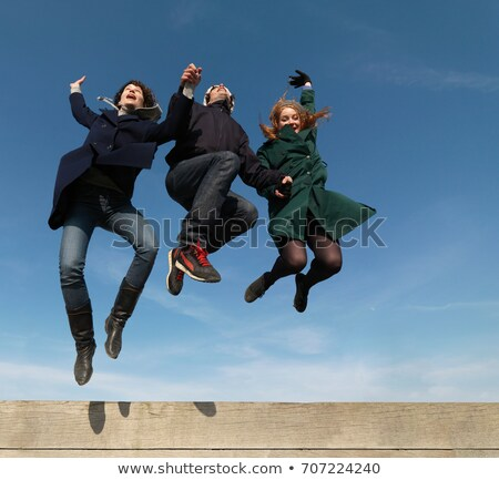 Friends leaping across wooden obstacle Stock photo © IS2