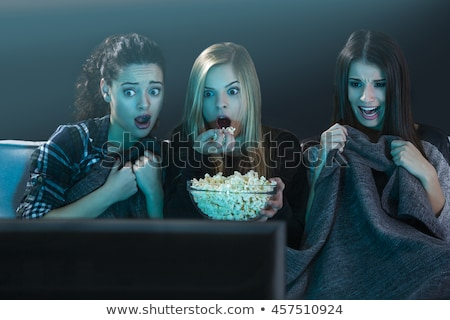 woman watching a scary movie and eating popcorn stock photo © studiostoks