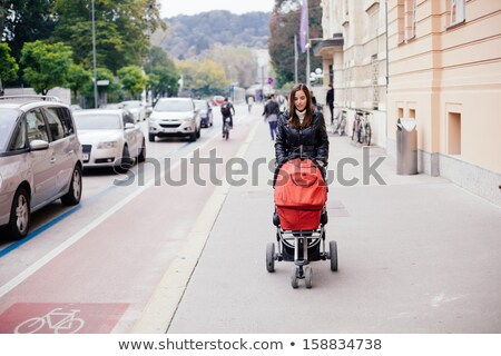 Young girl pushing buggy on pavement Stock photo © IS2