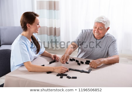 Caretaker And Senior Man Playing Dominoes Stock photo © AndreyPopov
