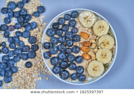 Dietary natural breakfast with fresh organic ingredients - berries, granola, banana in a glass on a  Stock photo © artjazz