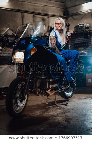 Female mechanic sitting in metal workshop looking into camera Stock photo © Kzenon