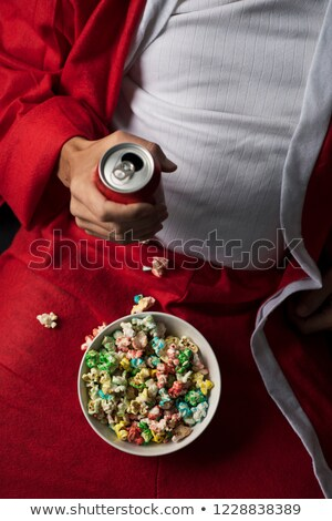 man in santa suit drinking beer and eating popcorn stock photo © nito