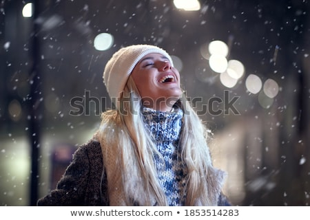Happy young woman walking outdoors in evening wearing hat and scarf. Stock photo © deandrobot