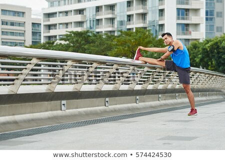 Confident young asian man jogging at the park Stock photo © deandrobot