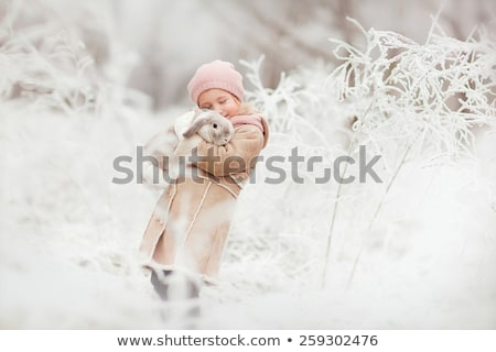 Little girl in winter pink hat in snow forest. Stock photo © Lopolo