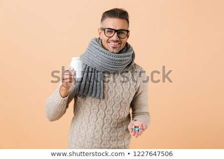 close up of a happy young man dressed in sweater stock photo © deandrobot