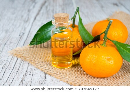 A bottle of tangerine essential oil with tangerines Stock photo © madeleine_steinbach