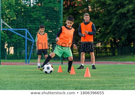 boy soccer player in training boy running between cones stock photo © matimix