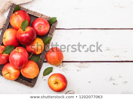Glass of fresh organic apple juice with red apples in vintage box on wooden background  Stock photo © DenisMArt