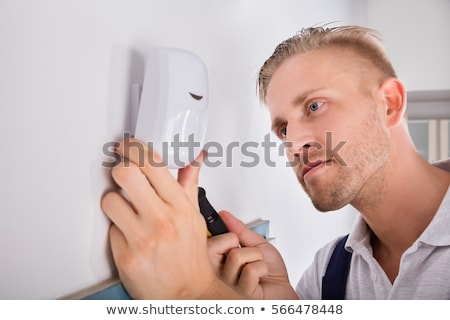 Electrician Installing Security System Door Sensor On Wall Stock photo © AndreyPopov