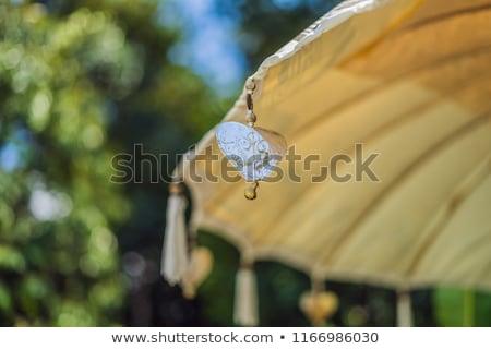 Traditional Balinese yellow sun umbrella with tassels Stock photo © galitskaya