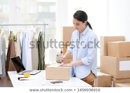 Young online shop manager with adhesive tape dispenser packing carton box Stock photo © pressmaster