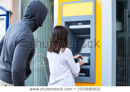 Thief Looking At Woman Entering The Pin In ATM Stock photo © AndreyPopov