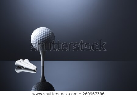 Golf ball on tee isolated on dark blue reflective background. Stock photo © lichtmeister