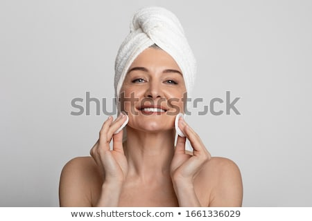 senior woman cleaning face by lotion on cotton pad Stock photo © dolgachov