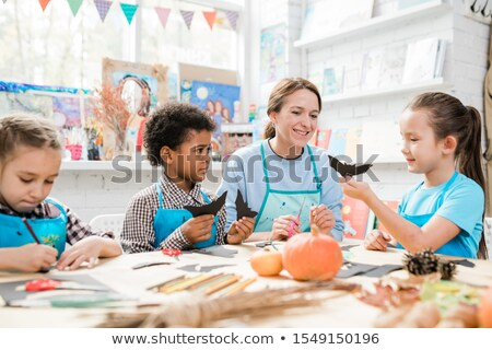 Diligent schoolkids making halloween toys and showing them to happy teacher Stock photo © pressmaster