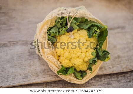 Cauliflower in a reusable bag on a stylish wooden kitchen surface. Zero waste concept Stock photo © galitskaya
