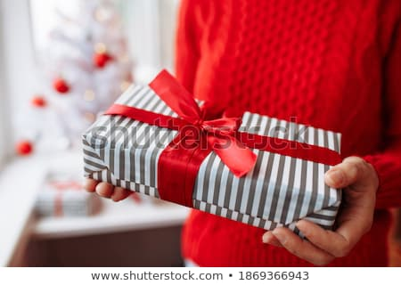 Smiling Young female holding Christmas Present Stock photo © dehooks