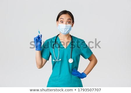 Smiling female doctor preparing a syringe on a white background stock photo © wavebreak_media