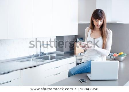 Kadın dizüstü bilgisayar kullanıyorsanız mutfak çekici genç kadın ev Stok fotoğraf © studiofi
