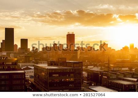 Pôr do sol cityscape dramático nuvens laranja amarelo Foto stock © elwynn
