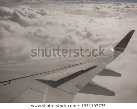 Aircraft right side wing, airplane flying over clouds in a blue sky Stock photo © lunamarina