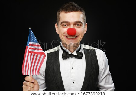 fashion young man holds a clowns red nose stock photo © feedough