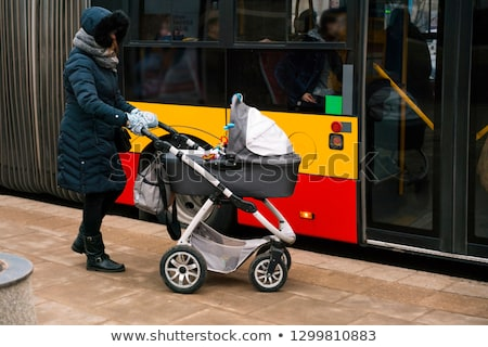Woman with stroller getting into a bus Stock photo © Kzenon