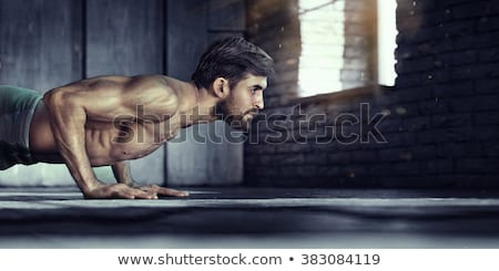 Muscular man doing push ups in gym Stock photo © deandrobot