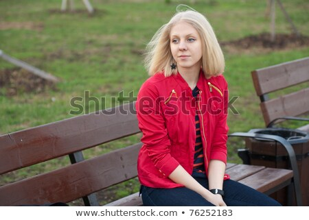 young woman sitting on a windy bench stock photo © dash
