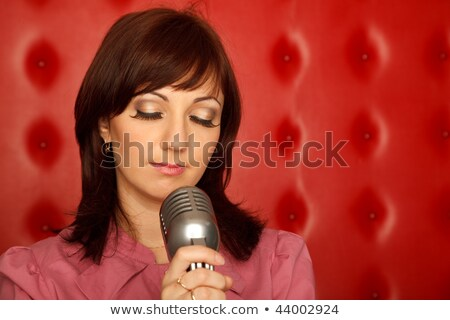 Portrait of girl in red shirt with microphone on rack against red wall. Horizontal format. Stock photo © Paha_L