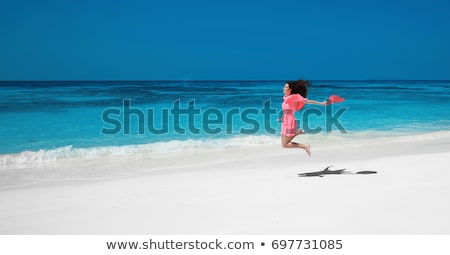 Enjoy life. Beautiful girl jumping running on exotic beach with  Stock photo © Victoria_Andreas