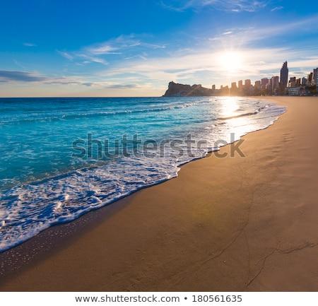 Stock fotó: Sziluett · naplemente · tengerpart · égbolt · víz · város